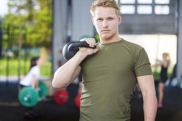 Confident man with kettlebell at fitness gym