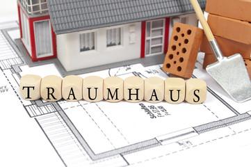 Bauplan mit Ziegelstein und Haus mit Traumhaus