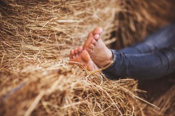 barefoot girl legs on haystack