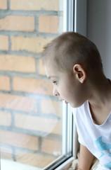 Мальчик смотрит в окно прислонившись к стеклу лбом