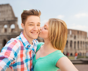couple kissing and taking selfie over coliseum