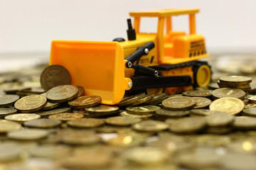 yellow toy bulldozer rakes rubles inflation in russia