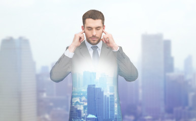 annoyed businessman covering ears with his hands