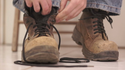 Male Putting On Old Workboot