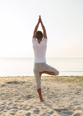 man making yoga exercises outdoors from back
