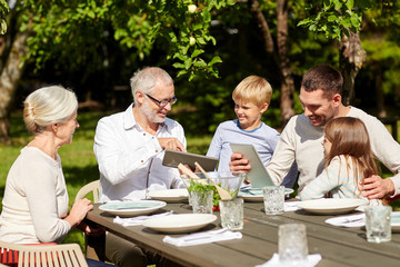 happy family with tablet pc at table in garden