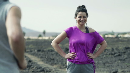 Happy woman smiling and man jogging on desert, slow motion