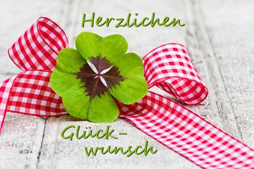 Kleeblatt mit Geschenkschleife auf Holz, Herzlichen Glückwunsch