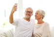happy senior couple with smartphone at home