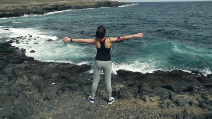 Woman standing on rocks by sea with wide open arms, slow motion