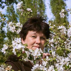 Portrait of mature woman among apple tree