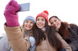 happy teenage girls taking selfie with smartphone