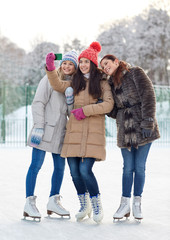 happy young women with smartphone on skating rink