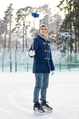 happy young man with smartphone on ice rink