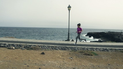 Young woman jogging through boardwalk by sea, slow motion