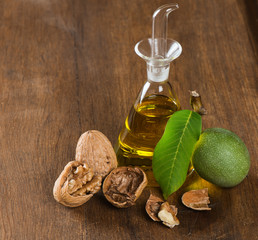 Walnuts in green husk with leaf and oil