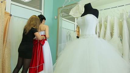The bride wears a dress in the bridal salon