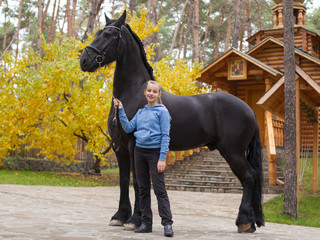 Smiling girl with a black horse