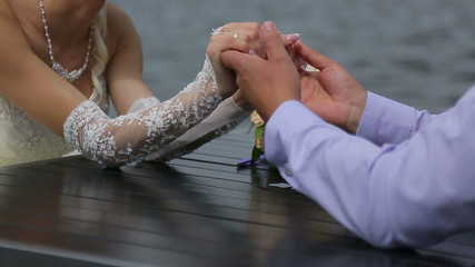 Bride and groom sitting at a table on the waterfront and holding