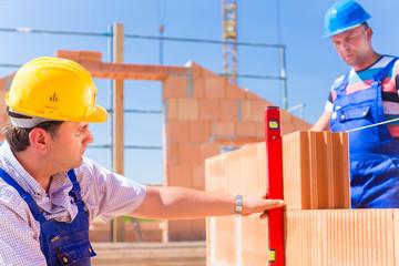 Zwei Handwerker kontrollieren Wände auf einer Baustelle