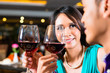 Close up of Asian couple toasting with red wine