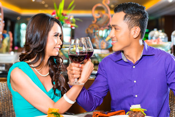 Asian couple toasting in restaurant