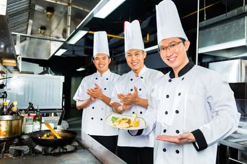 Asian Chefs in hotel restaurant kitchen