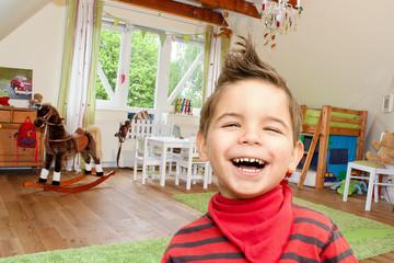 Kind lachend vor Kinderzimmer
