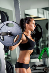 fitness girl with a barbell in the gym, crouches