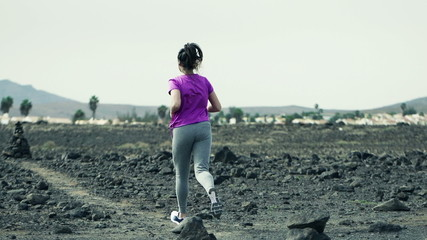 Young woman jogging on desert, slow motion shot at 240fps