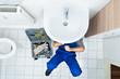 Leinwanddruck Bild - Plumber Repairing Sink In Bathroom