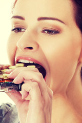 Young woman eating pills.