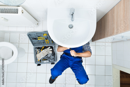 Leinwanddruck Bild Plumber Repairing Sink In Bathroom
