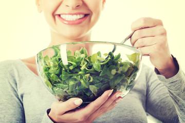 Beautiful woman eating lettuce.