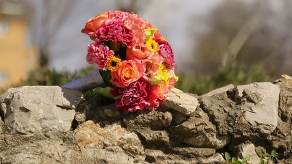 Bridal bouquet lying on the rocks in the park