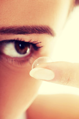 Woman putting lens into eye.