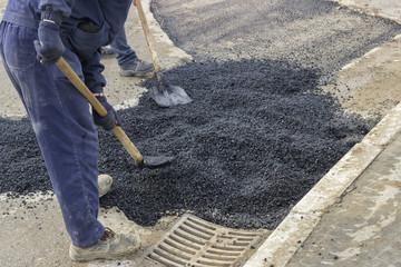 Asphalt workers with shovels patching asphalt 2