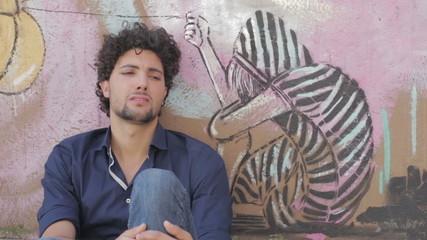 Sad, depressed young man  sitting near a graffiti wall