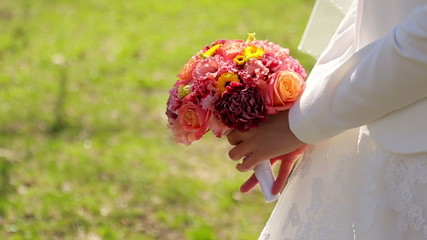 The bride holds a wedding bouquet in park