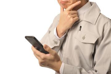 スマートフォンを活用している作業服の男性