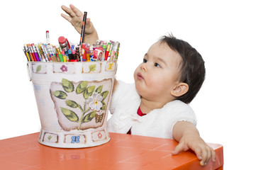 Little girl with a bucket of pencils at table