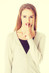 Beautiful woman with finger on lips.