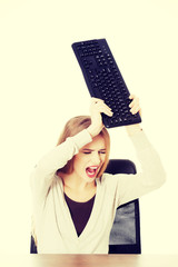 Beautiful woman trying to destroy keyboard.