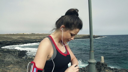 Young female jogger with smartwatch checking pulse by sea,