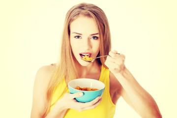 Beautiful caucasian woman eating cereals.