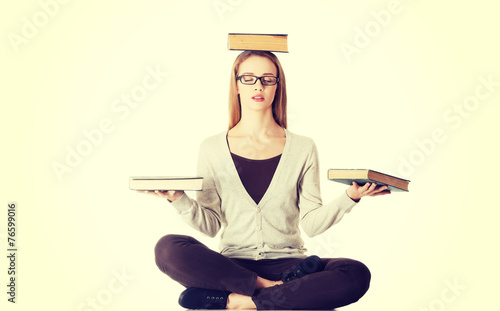 Beautiful casual woman sitting with books on head - 76599016