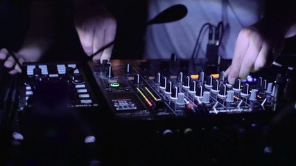 A DJ plays with the mixer in disco