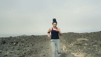 Portrait of happy woman jogging on desert