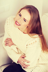Beautiful woman in sweater sitting on a couch.