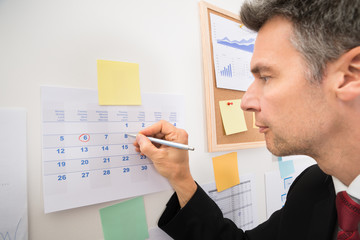 Businessman Highlighting The Important Dates